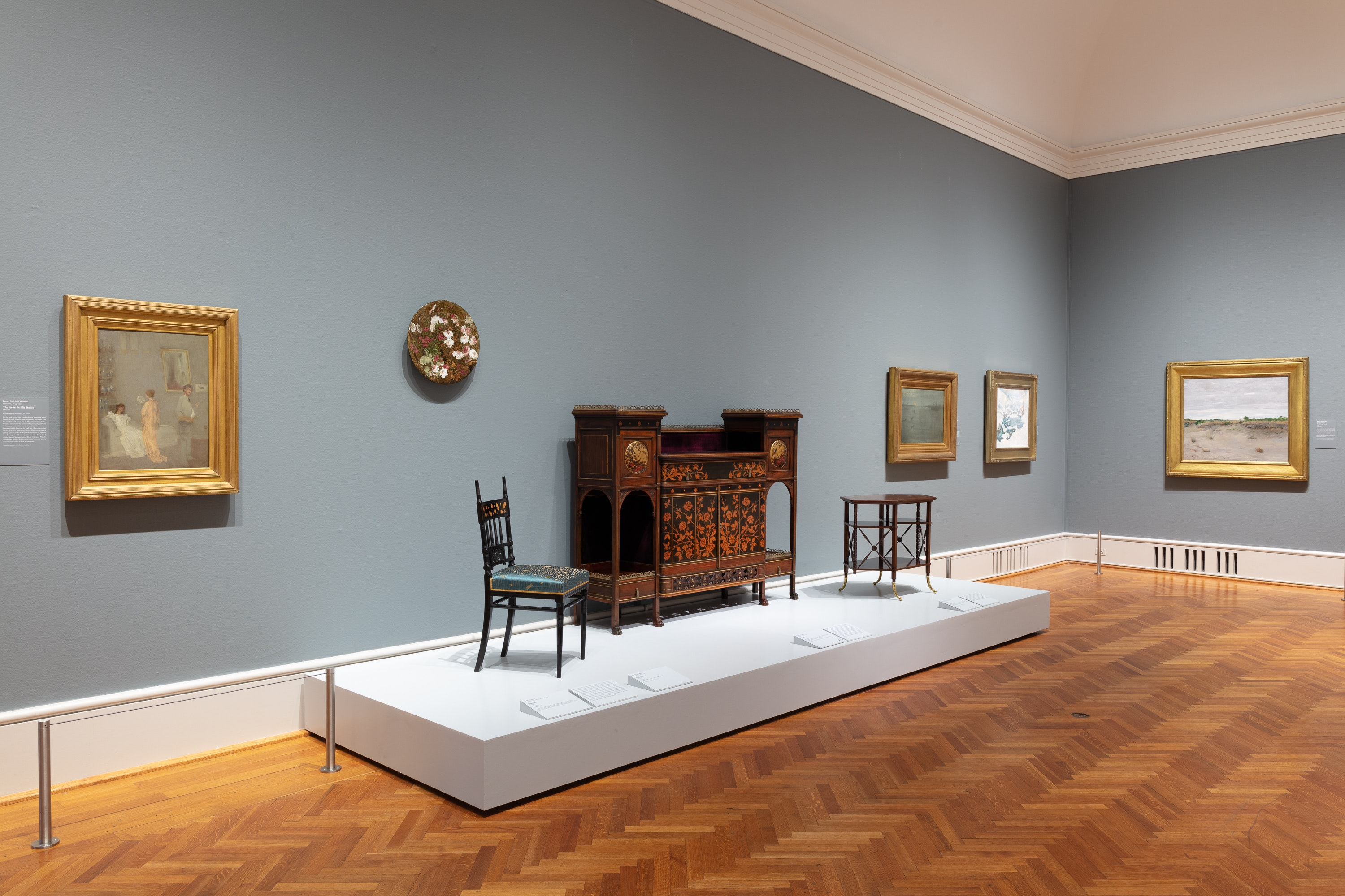Photo of wall in gallery 273 featuring paintings and furniture from the Gilded Age.