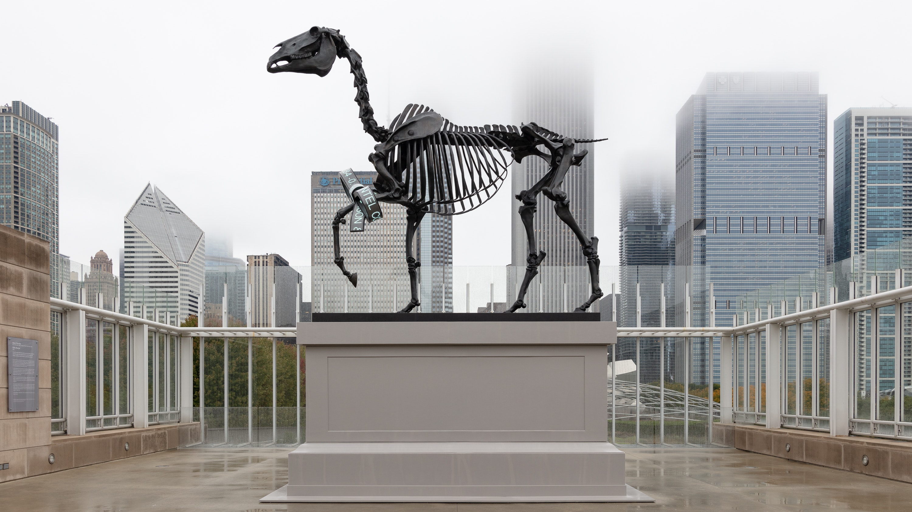 A bronze scultpure of a horse skelepton sits upon a large gray plinth. The entire sculpture is seen against the backdrop of Chicago's skyscrapers.