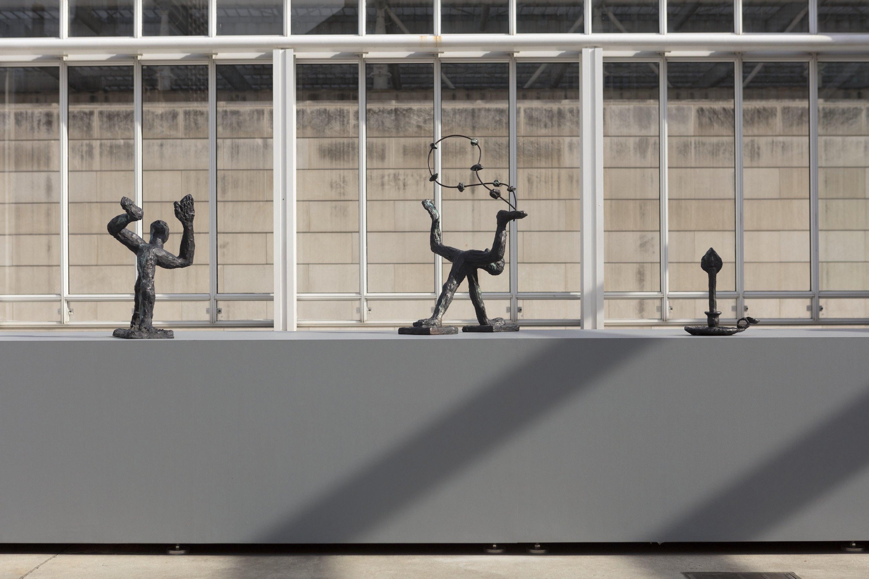 A close up view of bronze sculptures on a gray pedestal.
