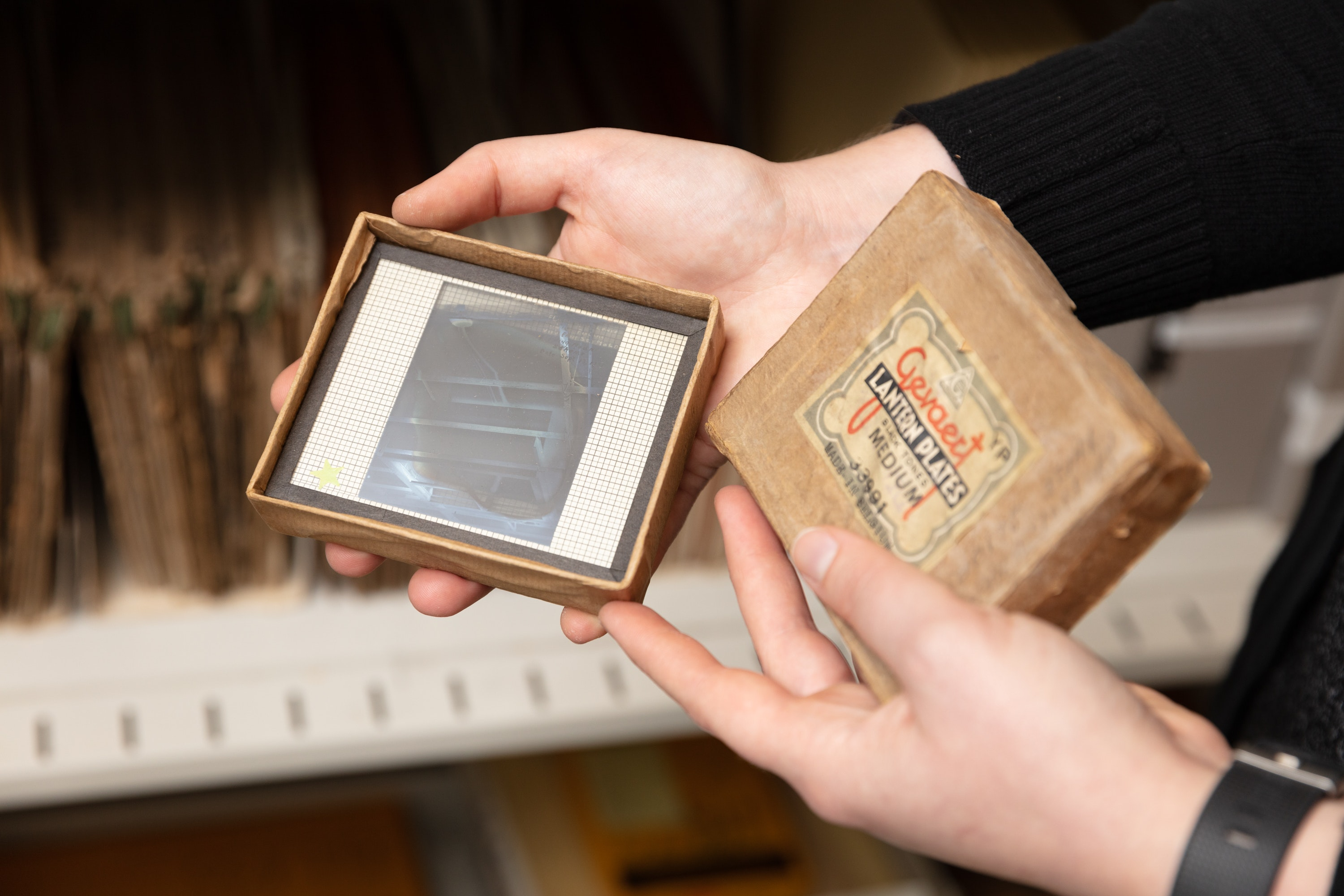 Archivist Shelby Silvernell holds an old glass negative called a Lantern Slide