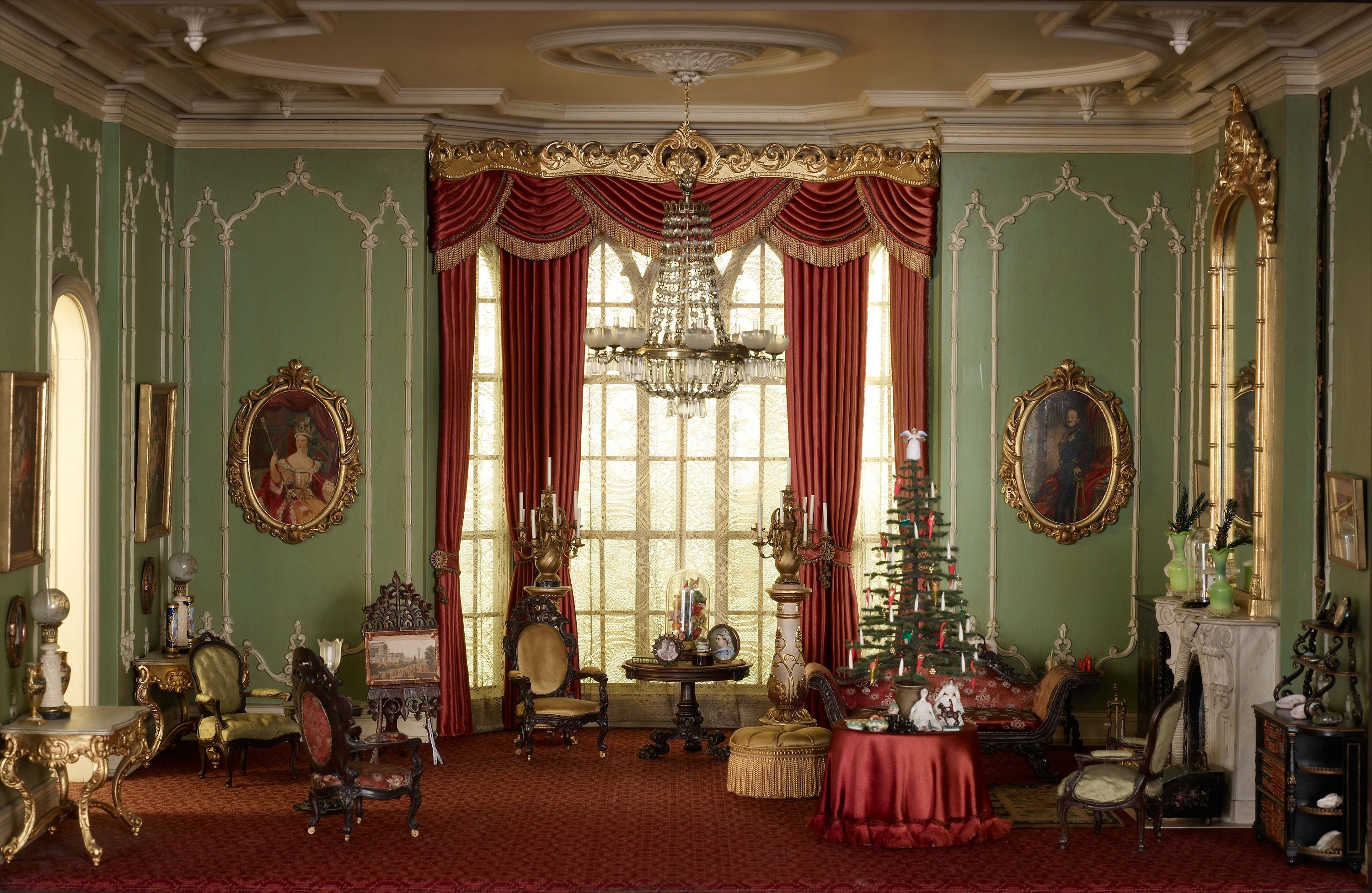 A photo of a miniature ornate English drawing room from the Victorian period decorated for the holidays. The room's green walls, red curtains and carpet, and gold ornamental decoration