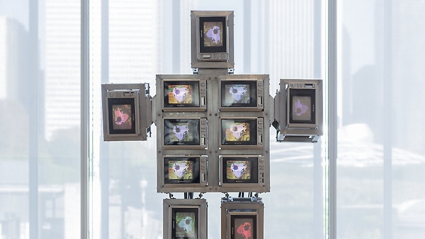Several screens stacked on top of one another to create a human form, each screen has a different video playing.