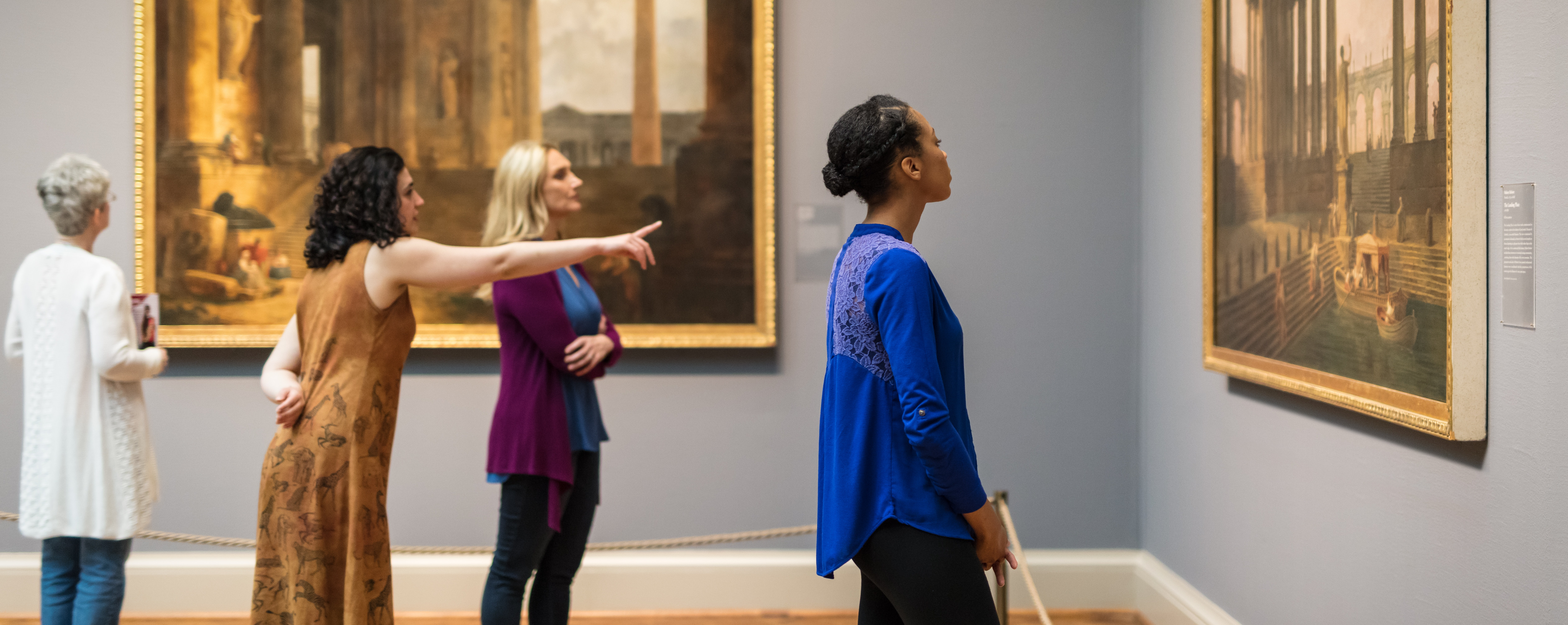 A group of women looking at classic artwork in the gallery