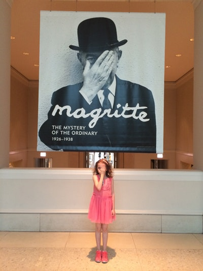 "A young girl in a pink dress standing below a large exhibition sign that says ""Magritte"""