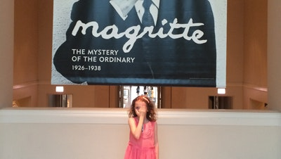 """A young girl in a pink dress standing below a large exhibition sign that says """"Magritte"""""""