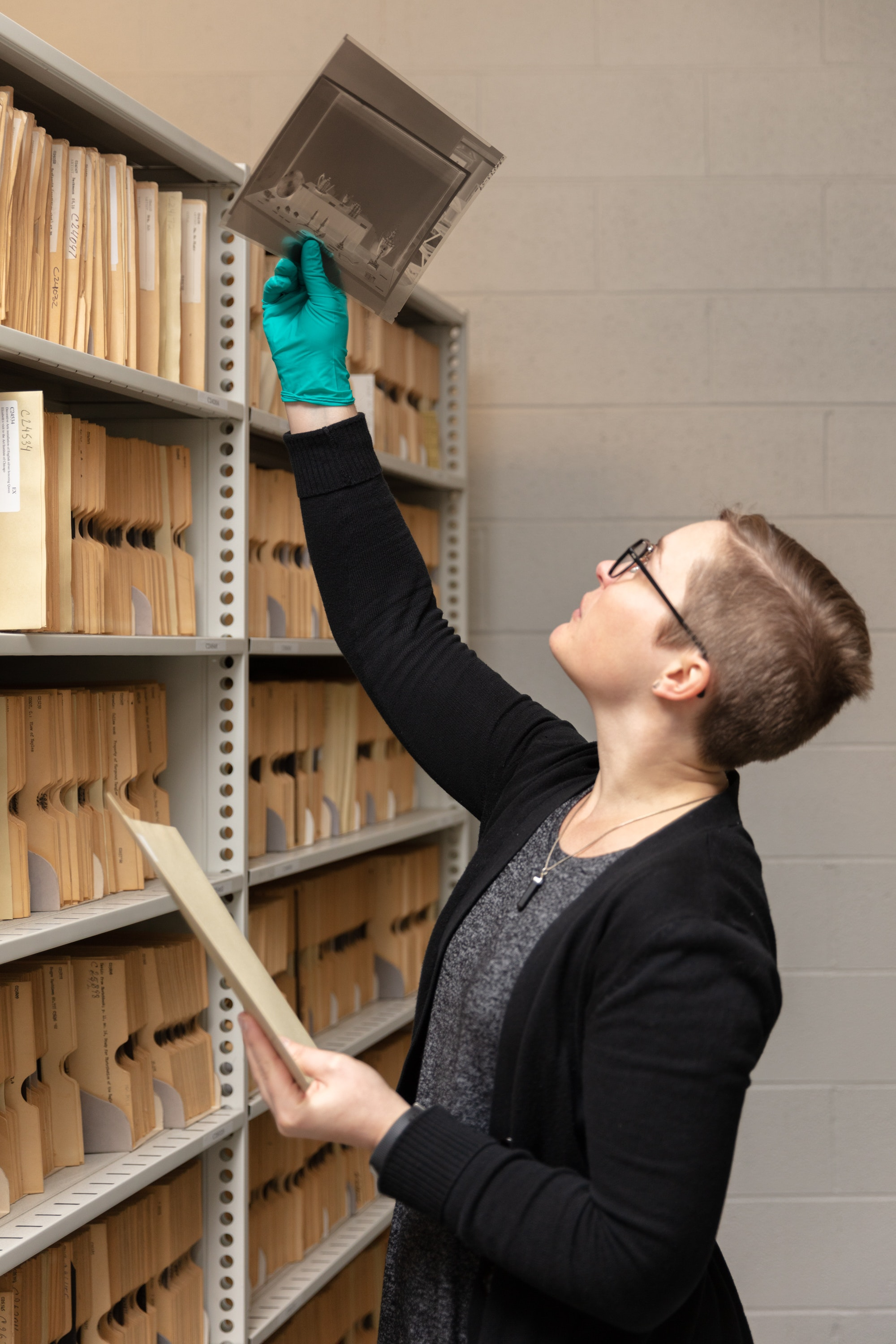 Archivist Shelby Silvernell holds on old large scale negative up to the light