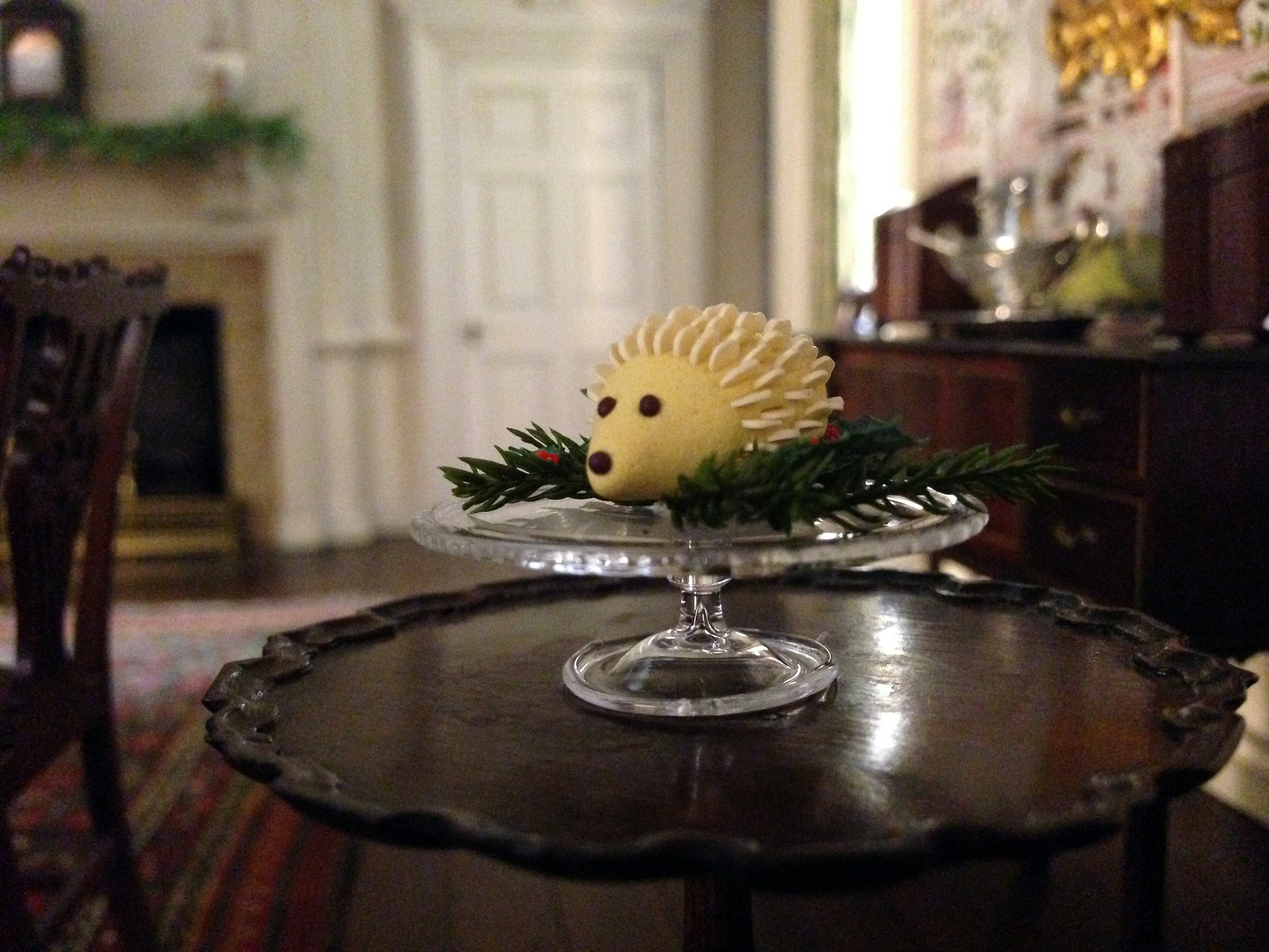 A photo of a tiny marzipan cake in the shape of a hedgehog on a glass platter on top of a round wooden table.