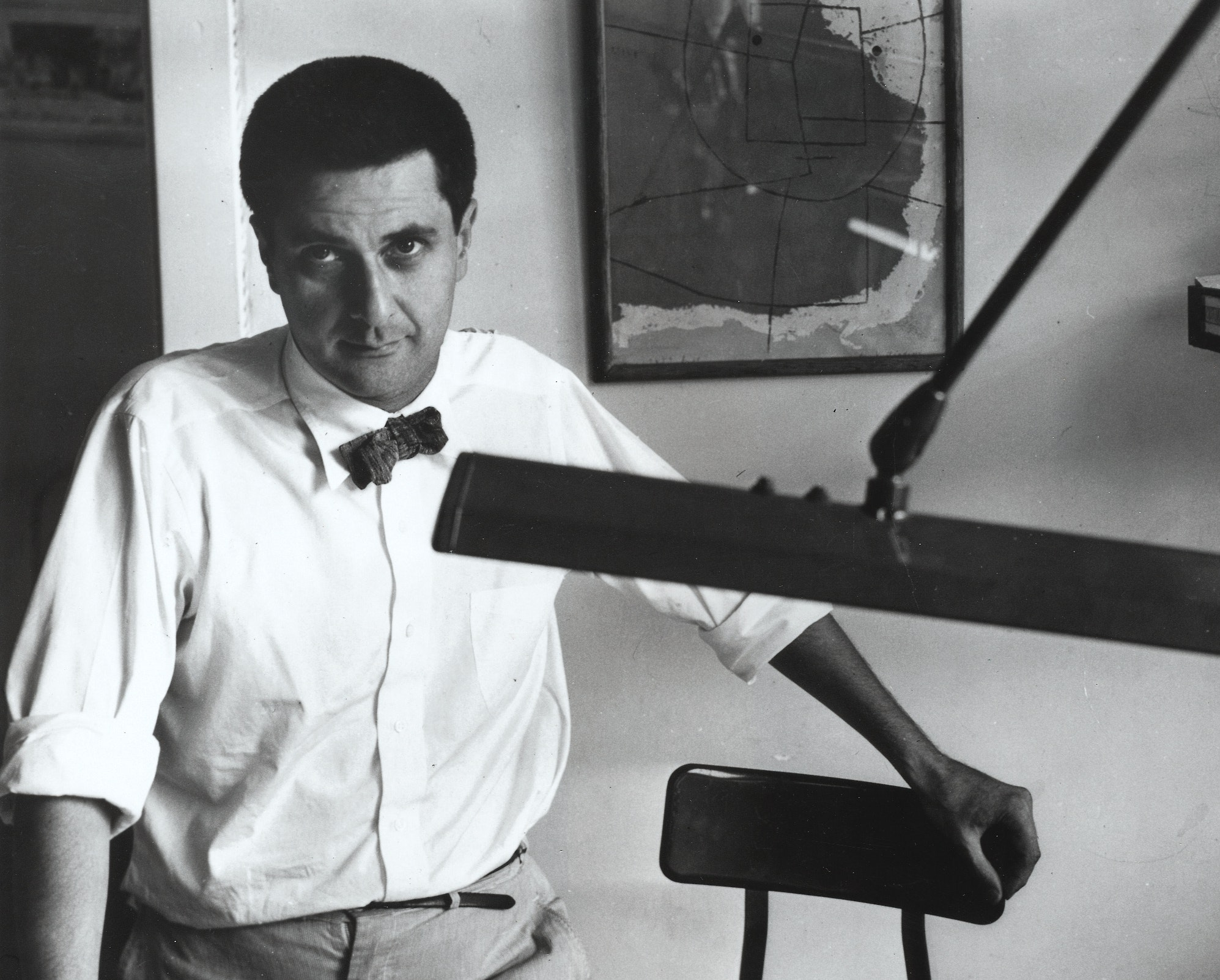 Black and white photo of Bertrand posing with architecture plans at a desk