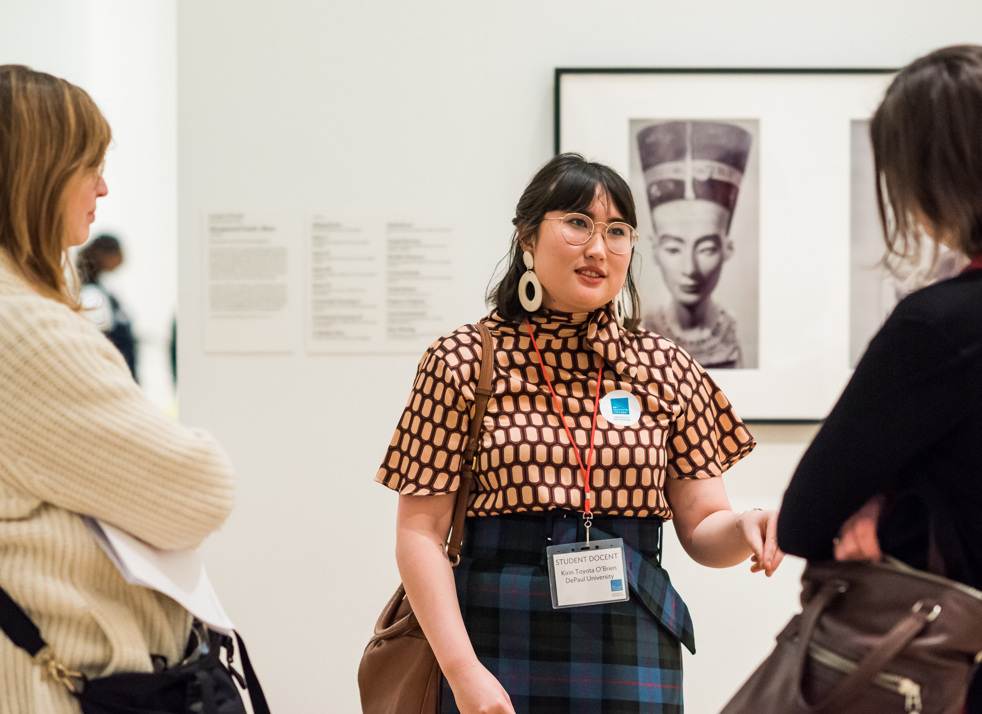 A young woman talks to two others about work in the collection.