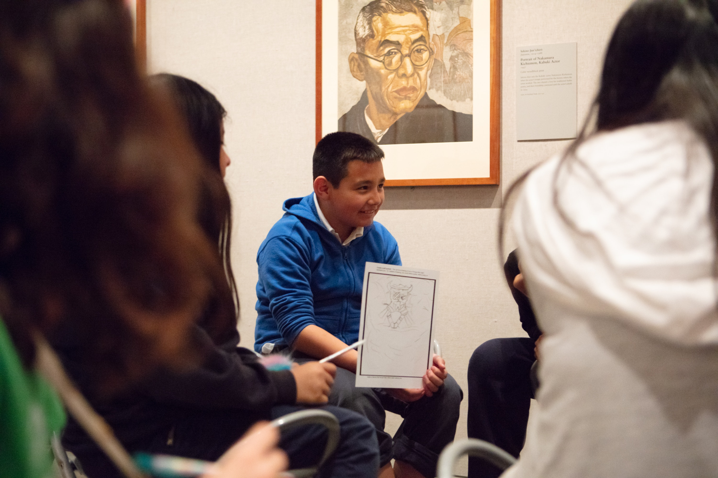 Young student holding a drawing he made in an exhibition of Japanese portraits