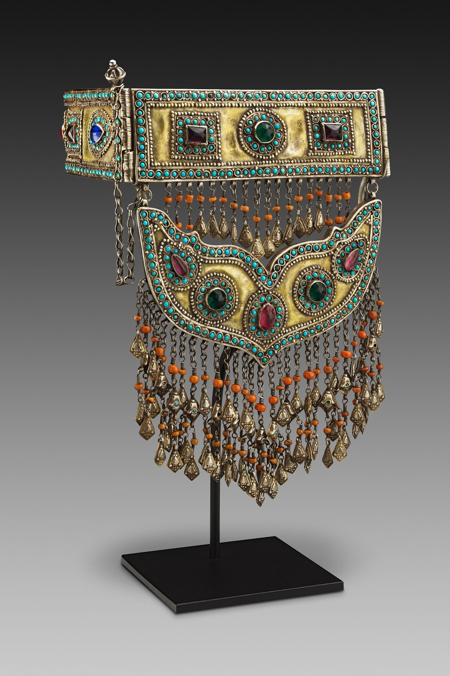 An ornate and colorful neckband with a bird pendant.