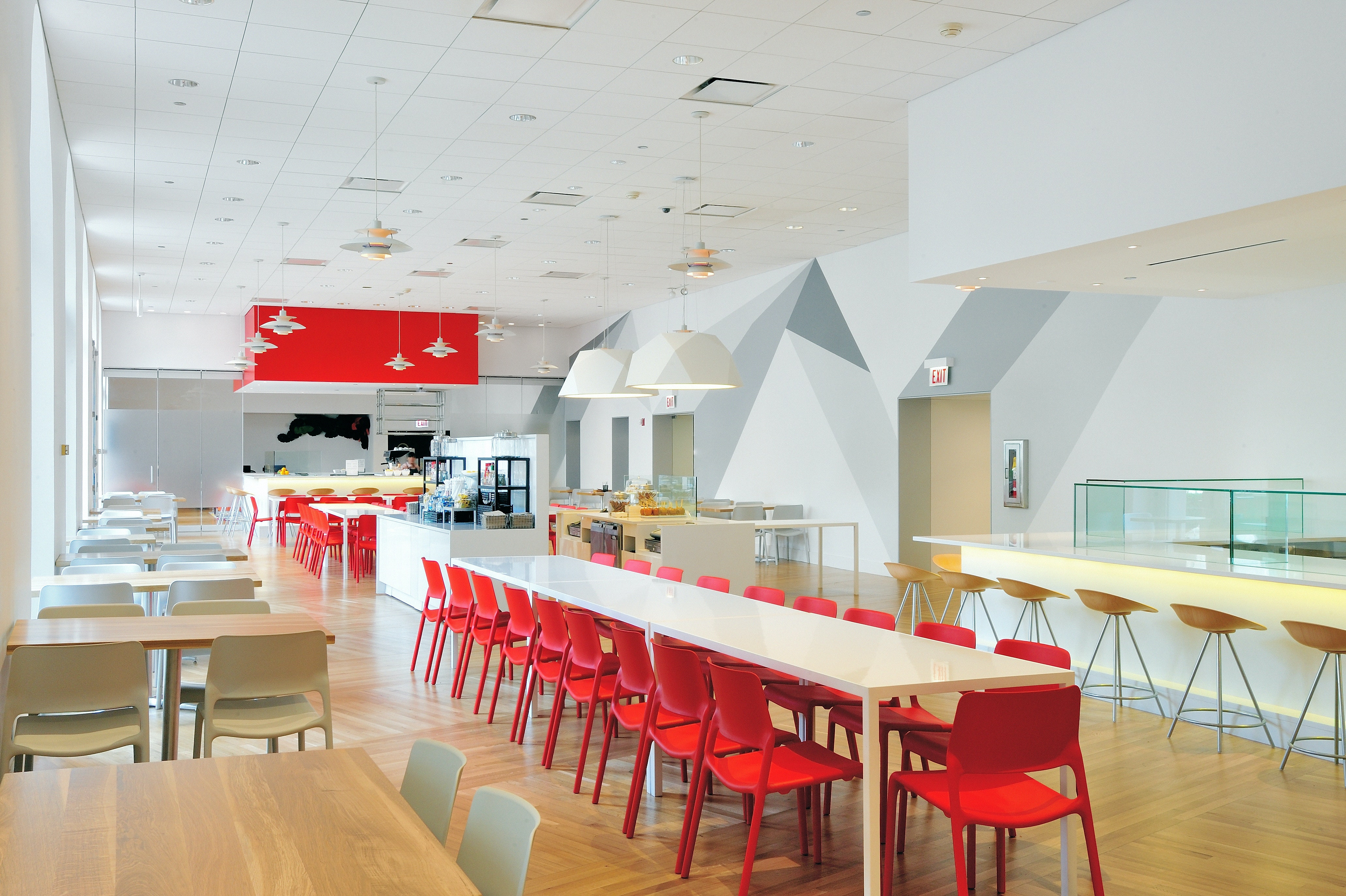 A long table with red chairs in a white room