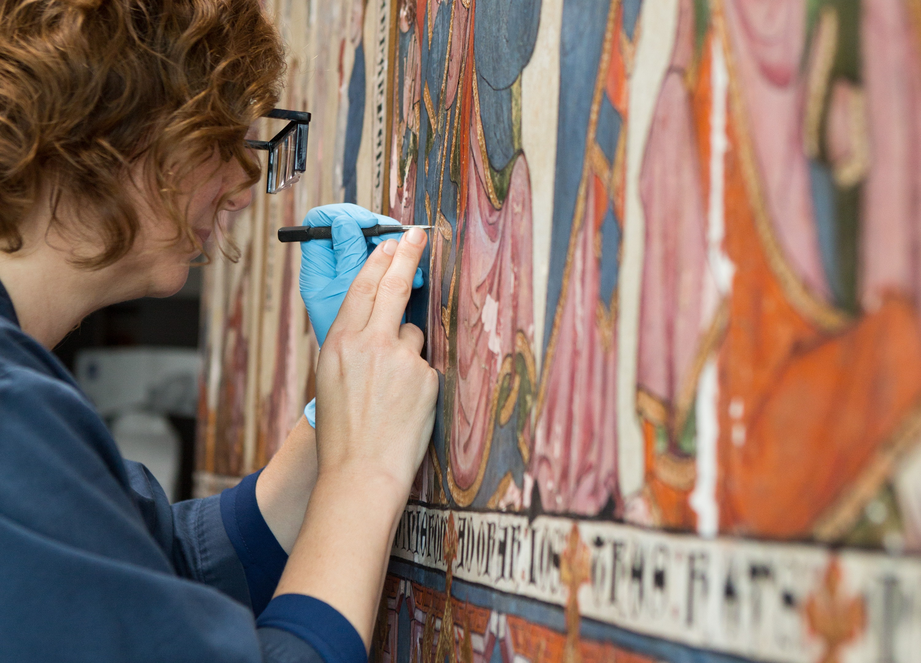 A conservator works on a large painting