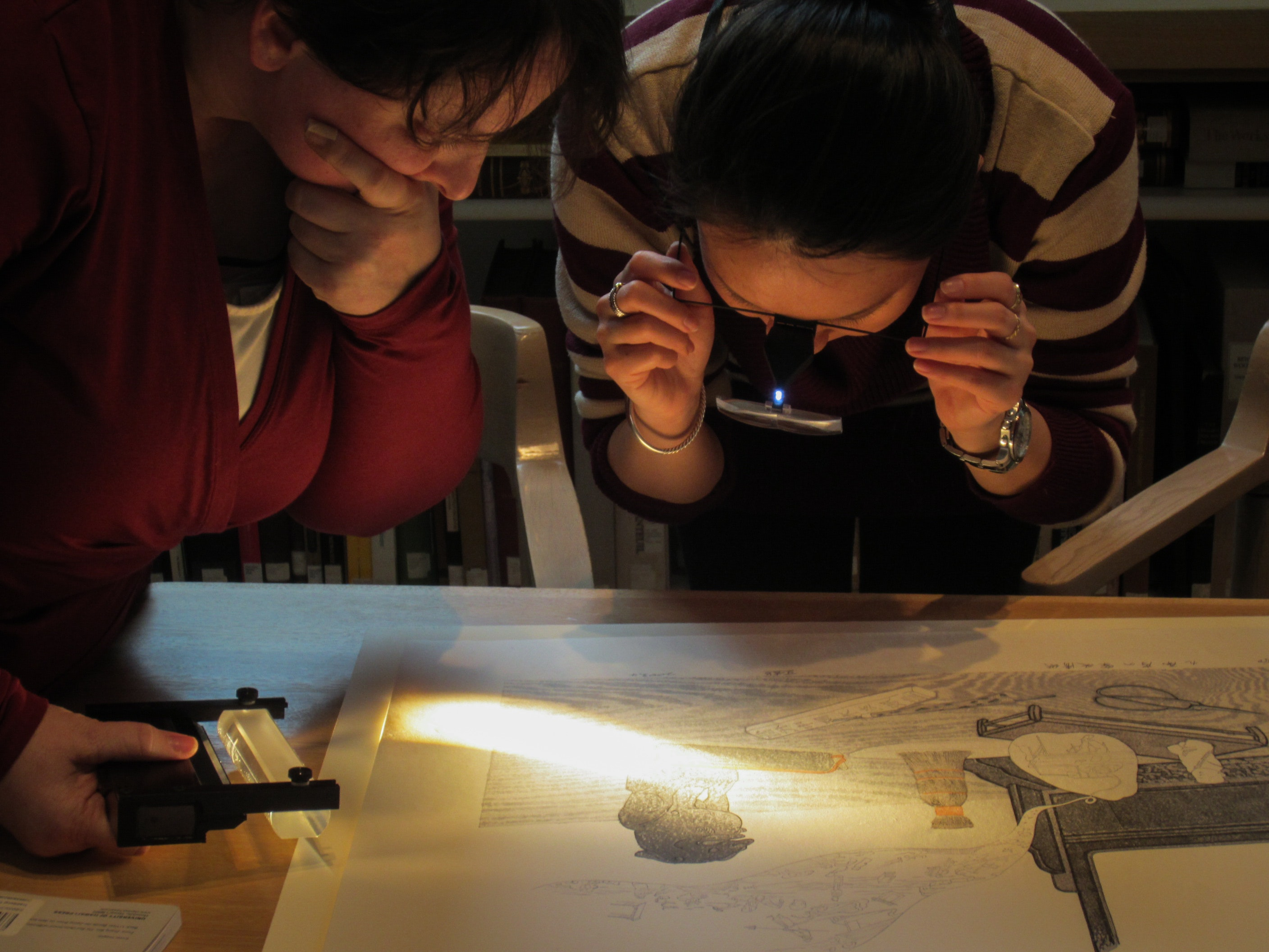 Two people look at an artwork under a magnifying glass