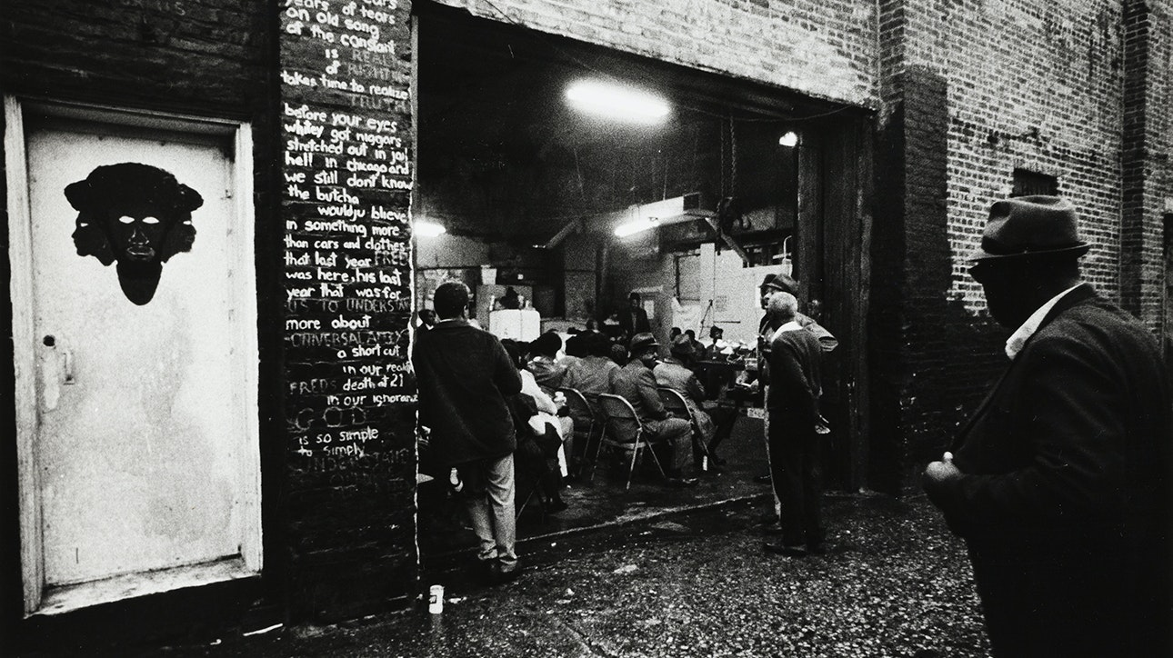 Black and white photograph looking from an alley into the Garage, where people are sitting and listiening to someone perform