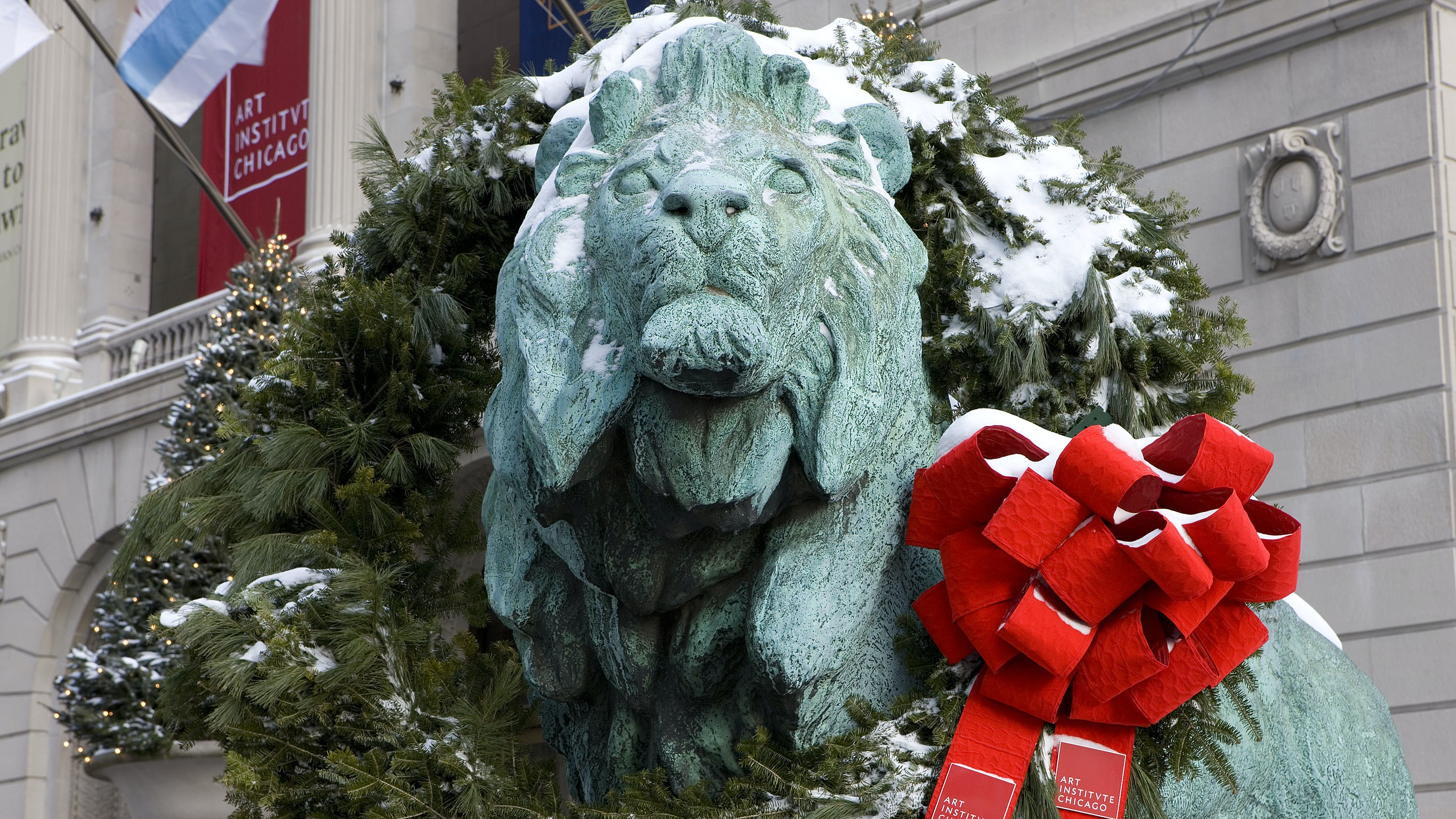 A bronze lion with snow-covered wreath