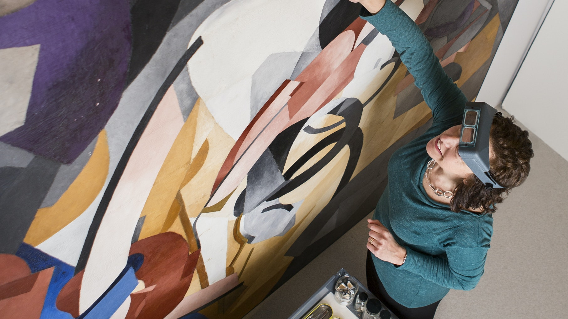 A conservator is seen from above treating a large abstract canvas by Francis Picabia.