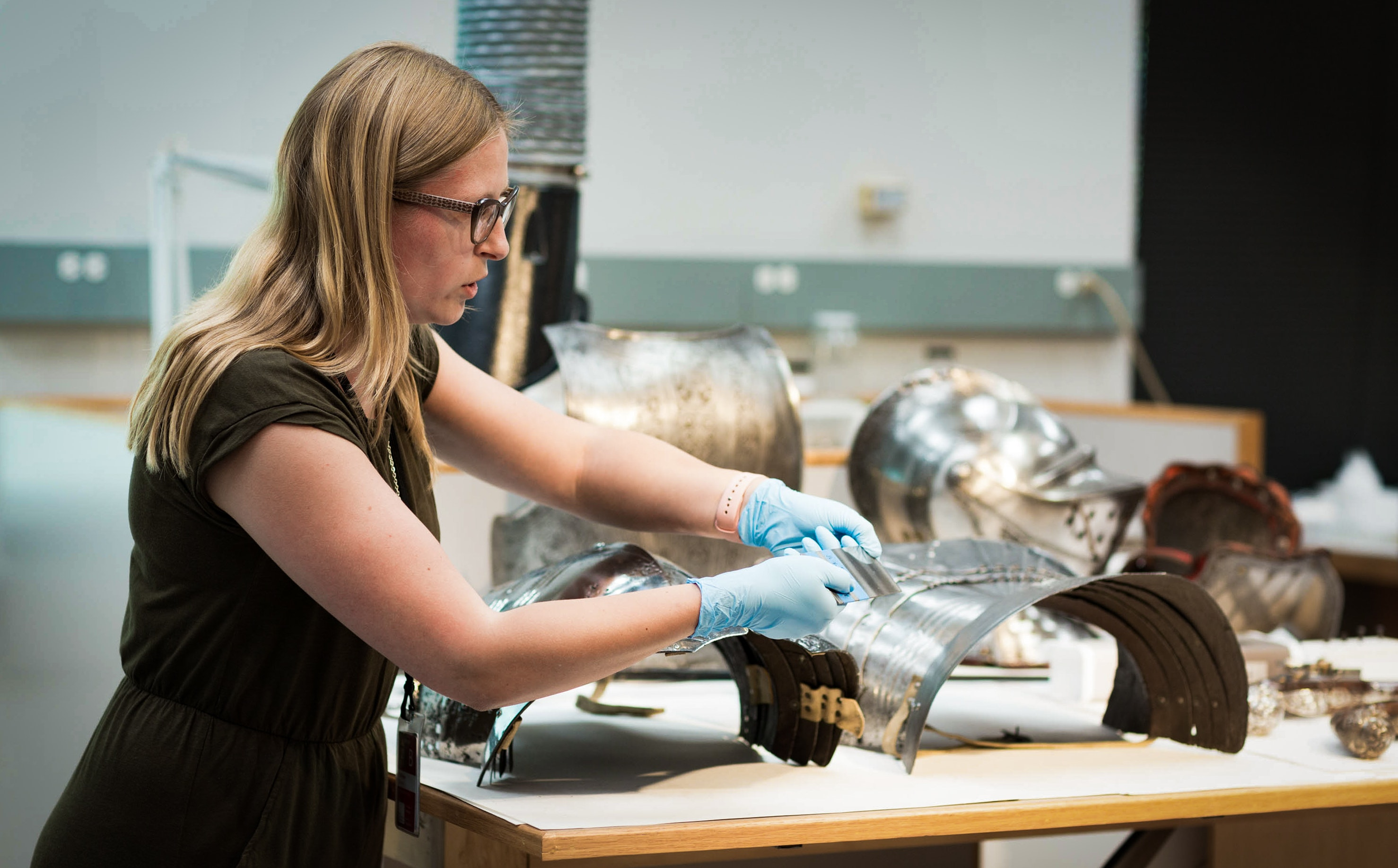 Conservator handling pieces of a suit of armor