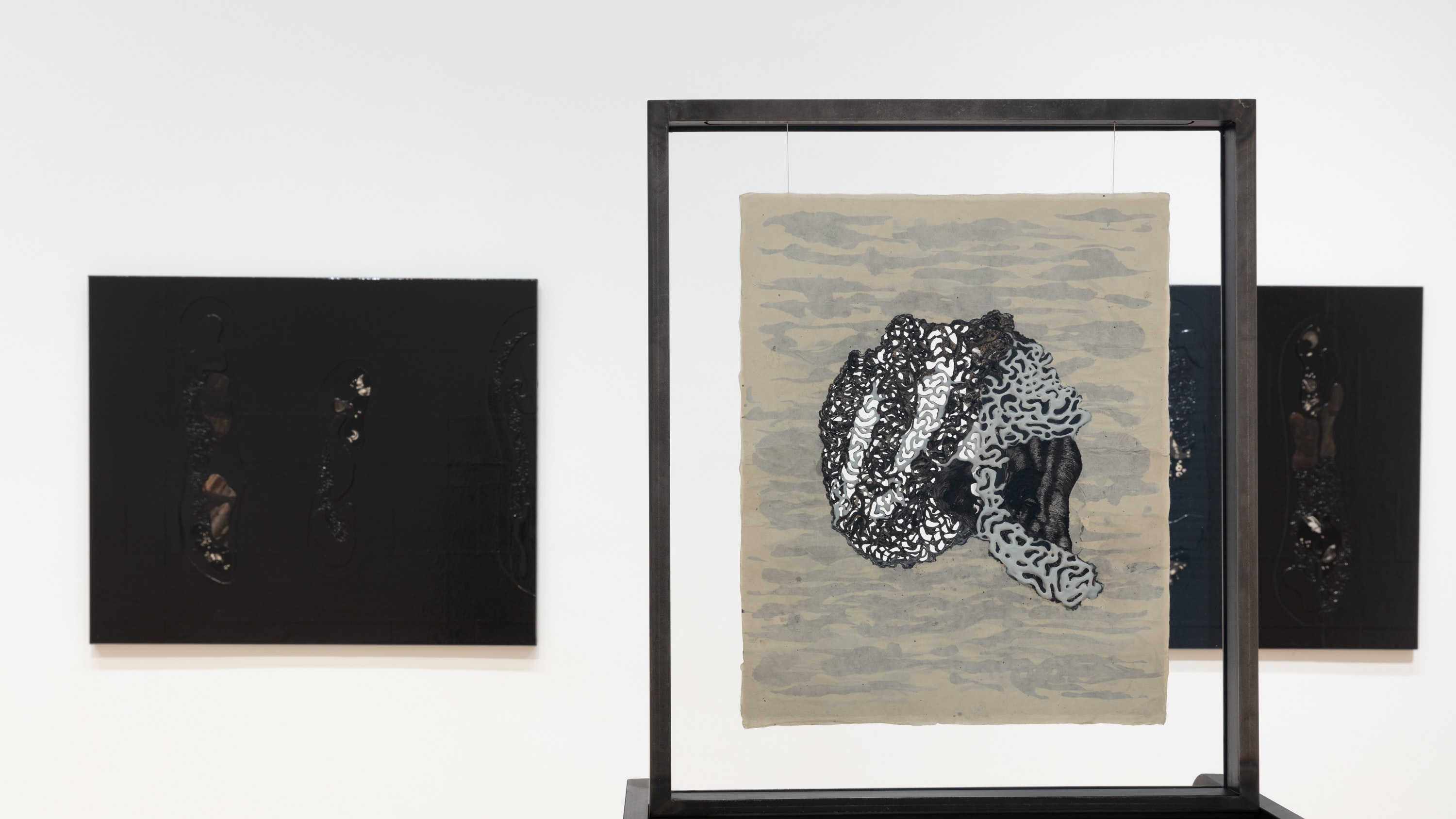 Installation view of two paintings and a drawing by Ellen Gallagher