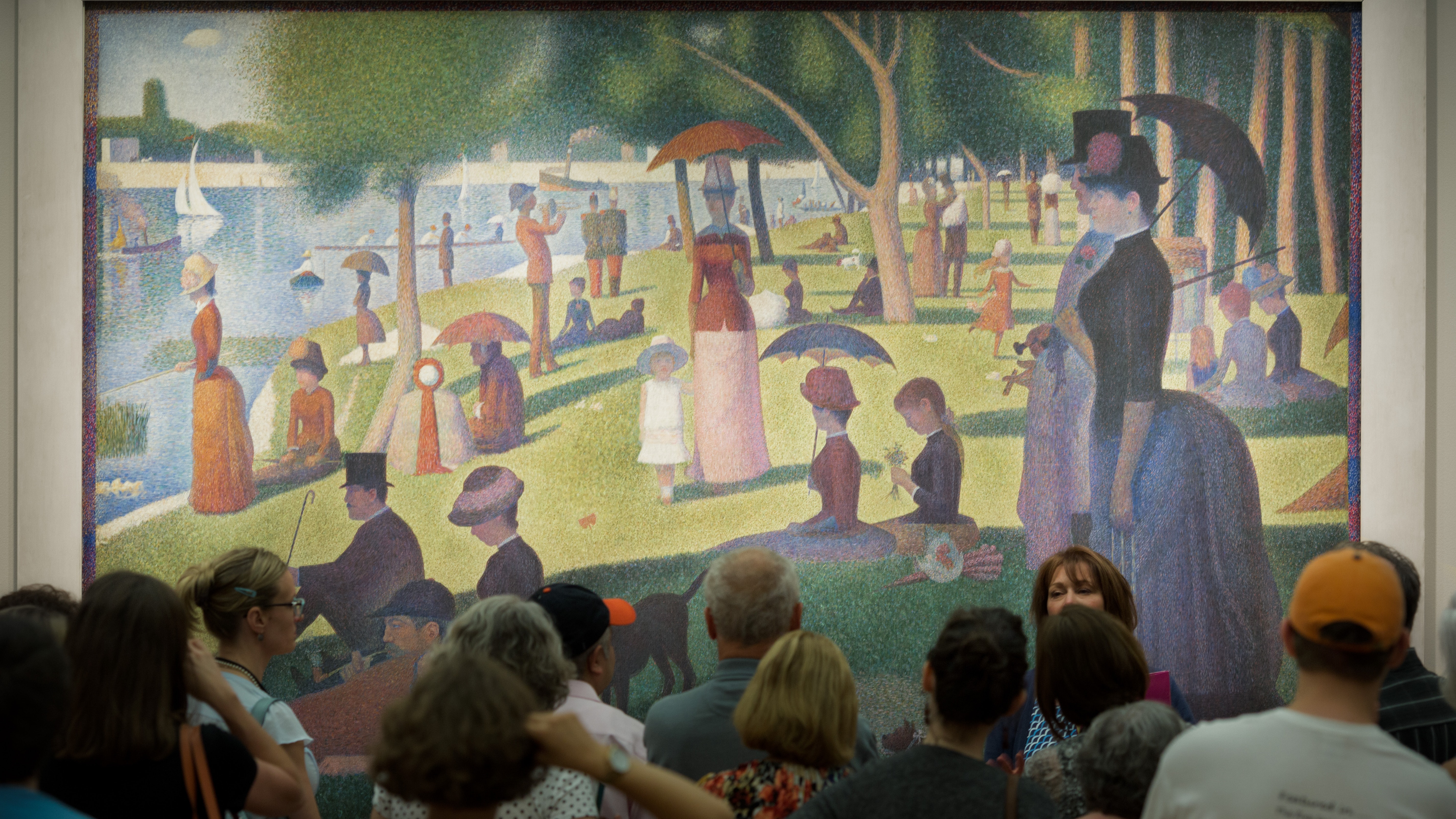 A group of visitors stands in front of Sunday on La Grande Jatte, a large Impressionist painting.