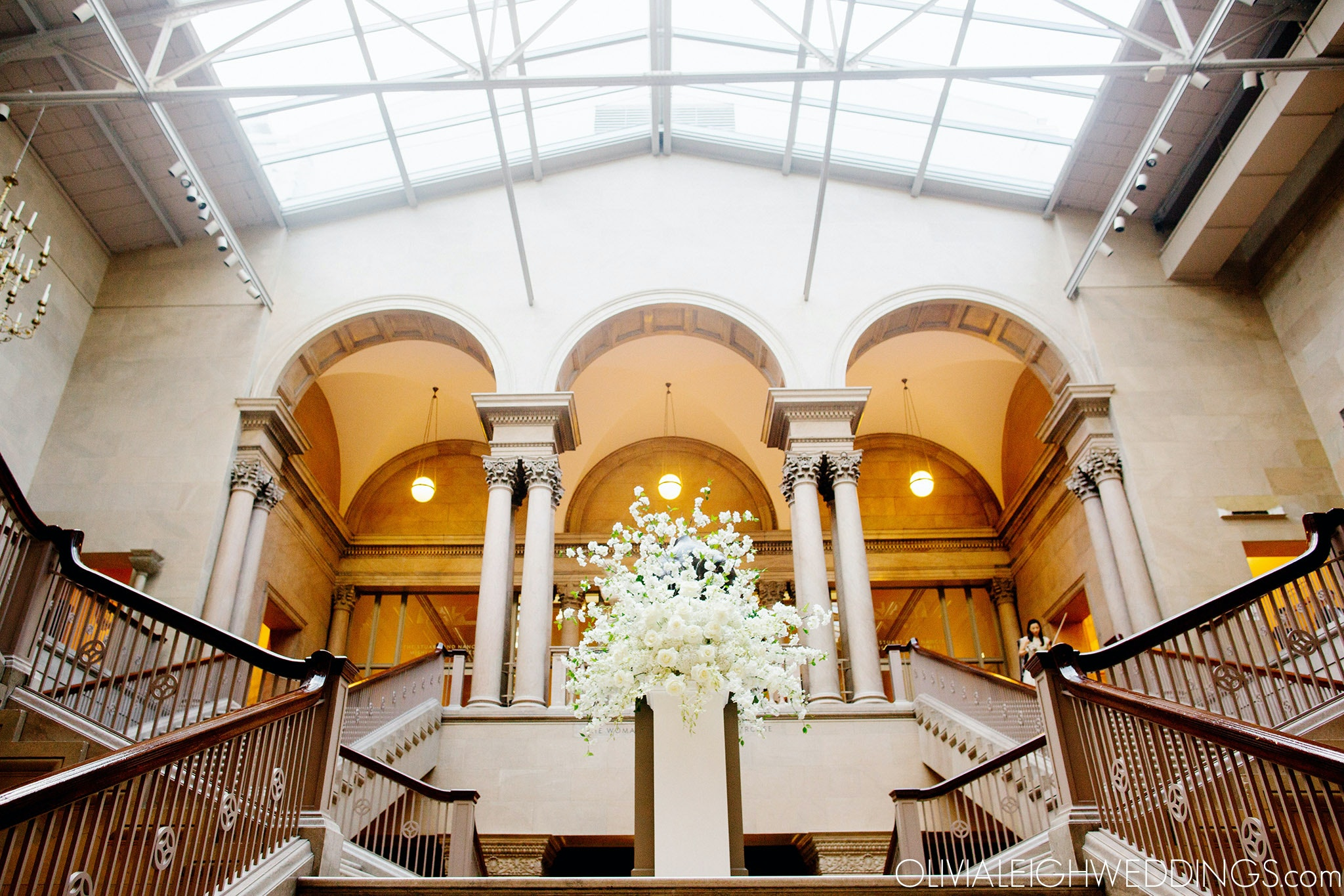 A large vase of flowers sites in the middle of a grandstaircase