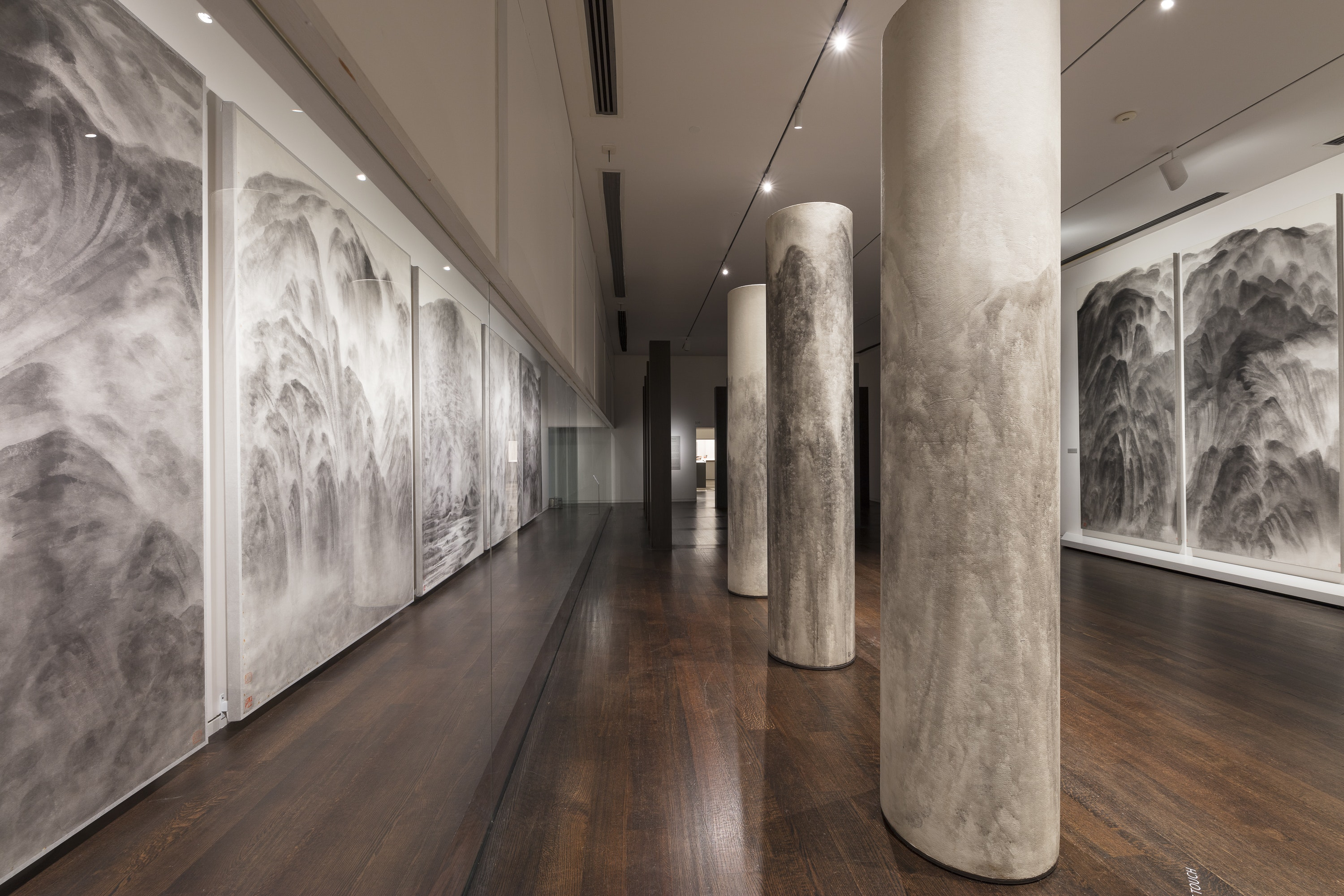 A picture of an installation of black and white panels and columns painted in black ink.