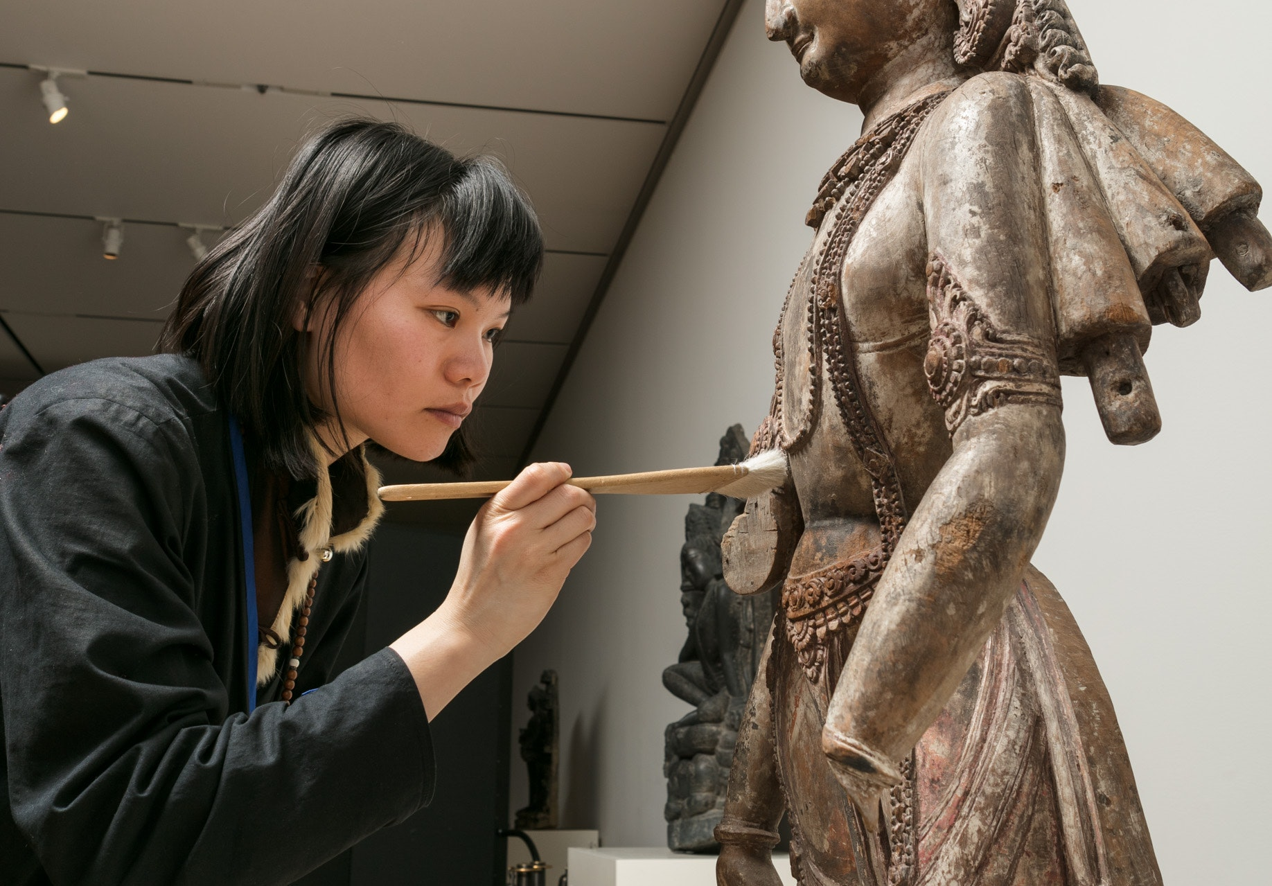 a conservator uses a brush to adjust an Asian sculpture