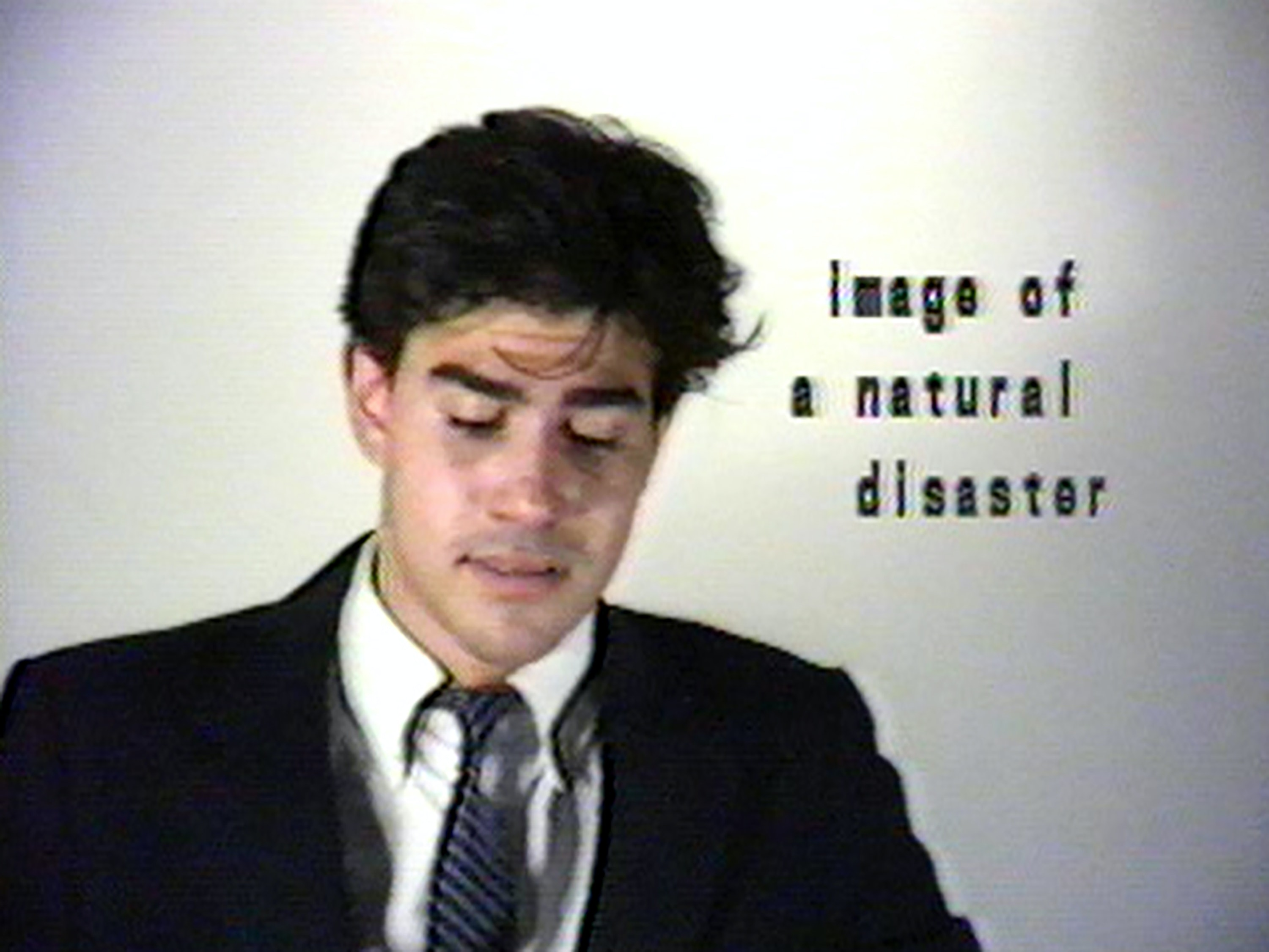 "A video shows a man in a suit and tie, appearing somewhat like a newscaster. The words ""image of a natural disaster"" appear in a space next to his head."