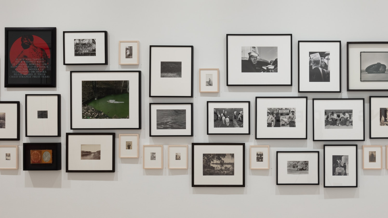 Wall of photographs from the collection selected by Dawoud Bey to accompany his exhibition Night Coming Tenderly Black