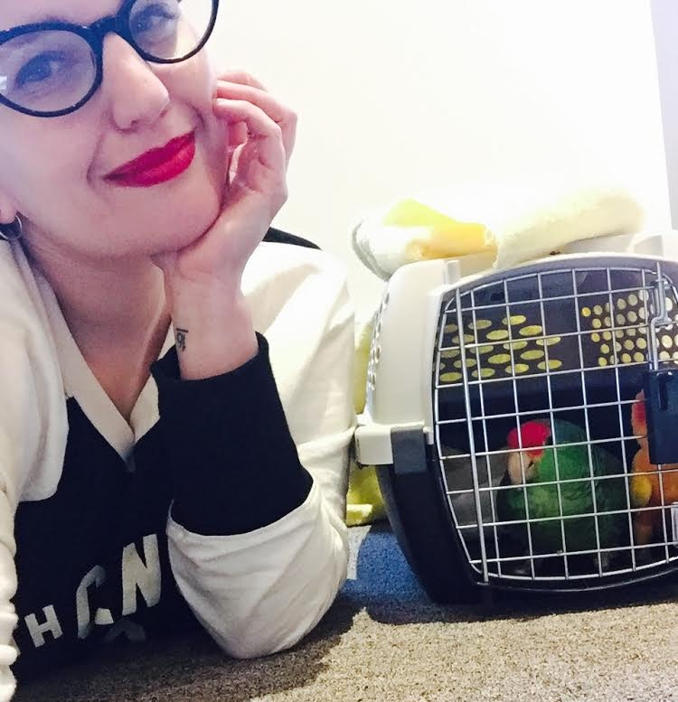 Blog post author poses with the parrots in their traveling case.
