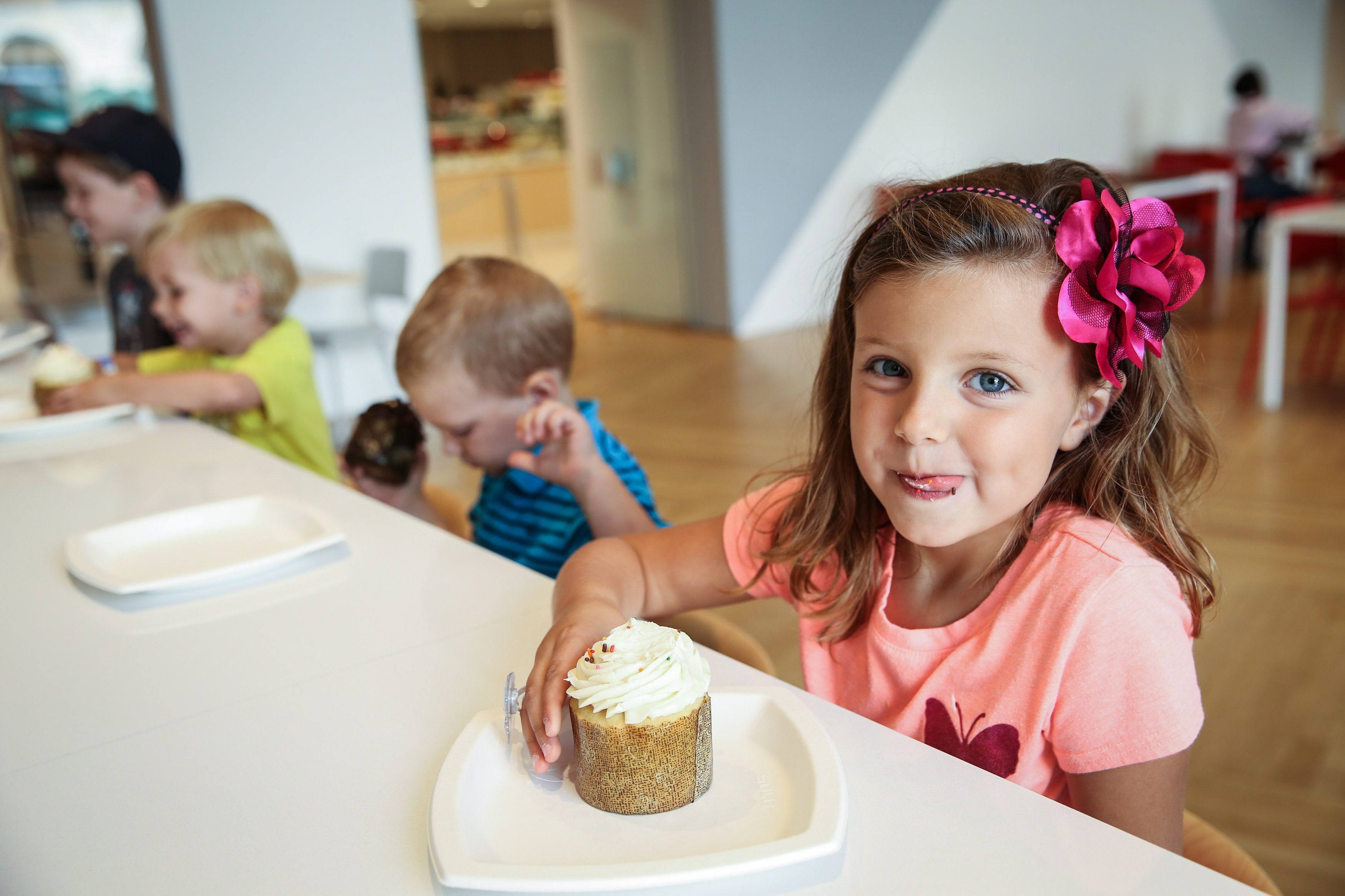 Four young children enjoy cupcakes