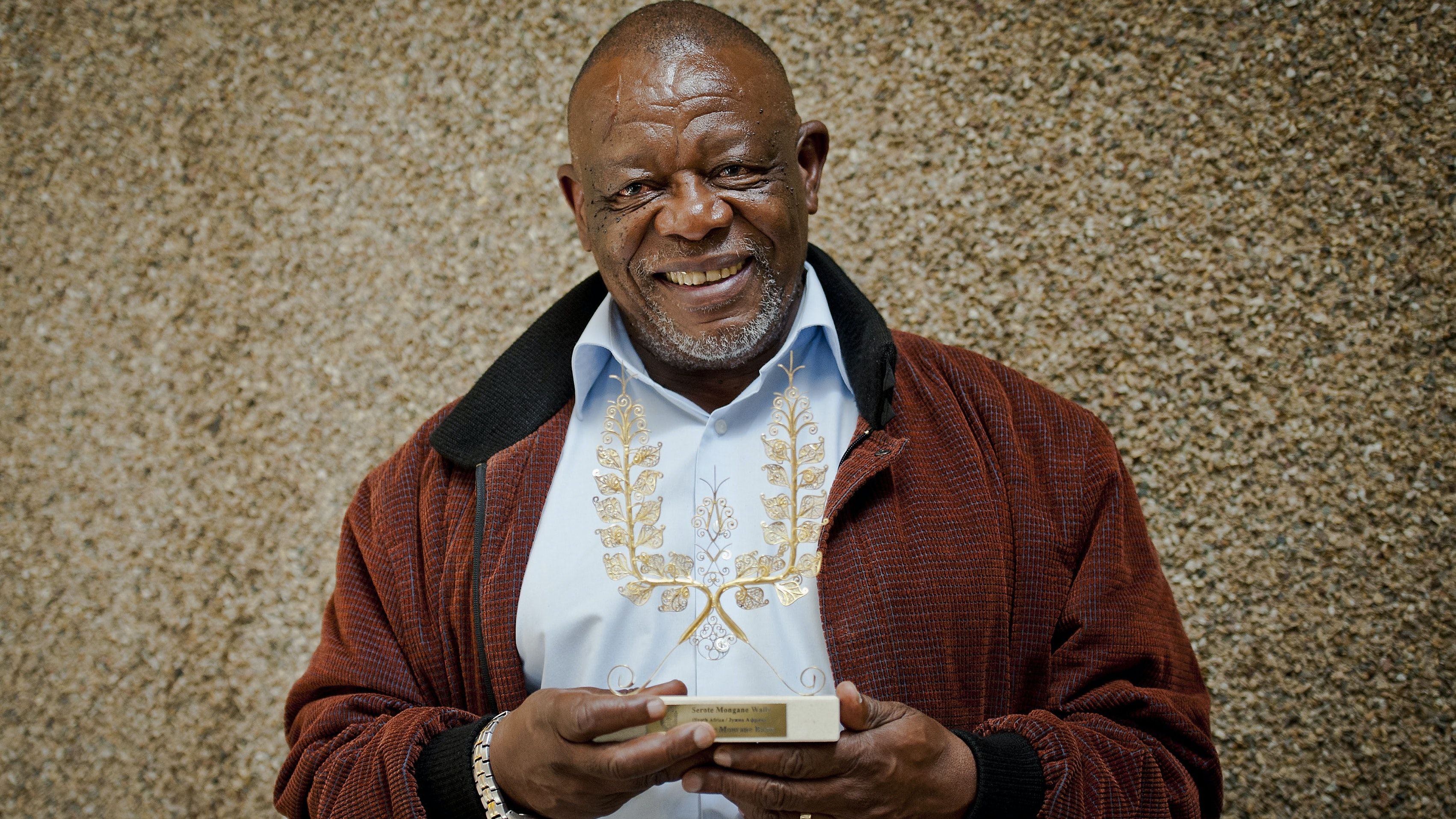 Image of poet and activist Dr. Mongane Wally Serote, a middle-aged gentleman wearing a brown jacket and blue shirt holding a gold award he had won for his poetry. The background is a gold wall.