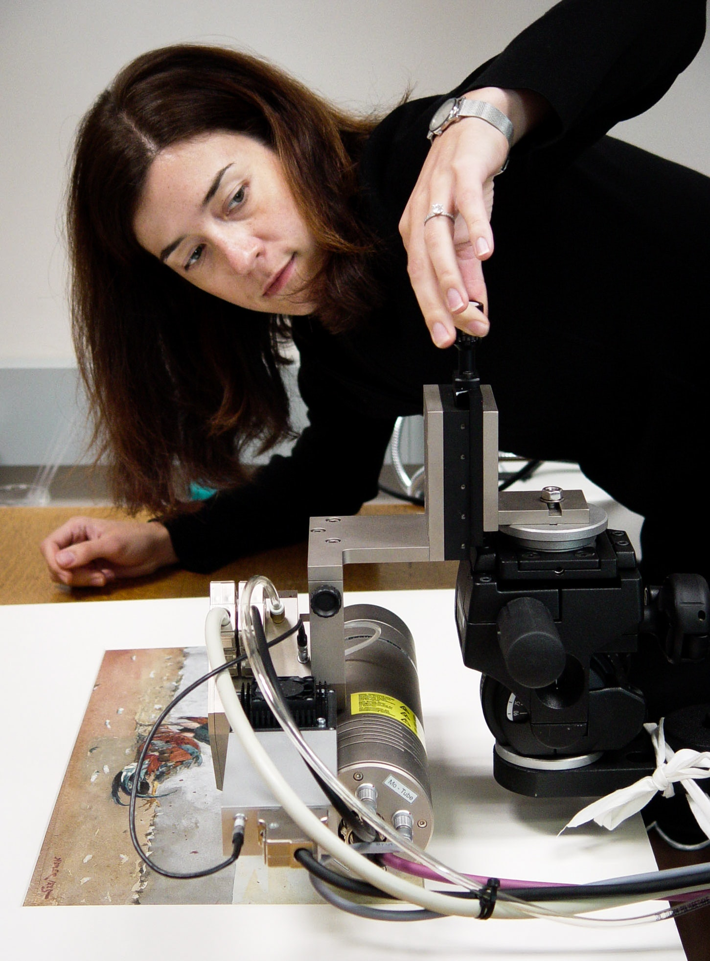 A conservator uses a machine to evaluate a print work on paper.