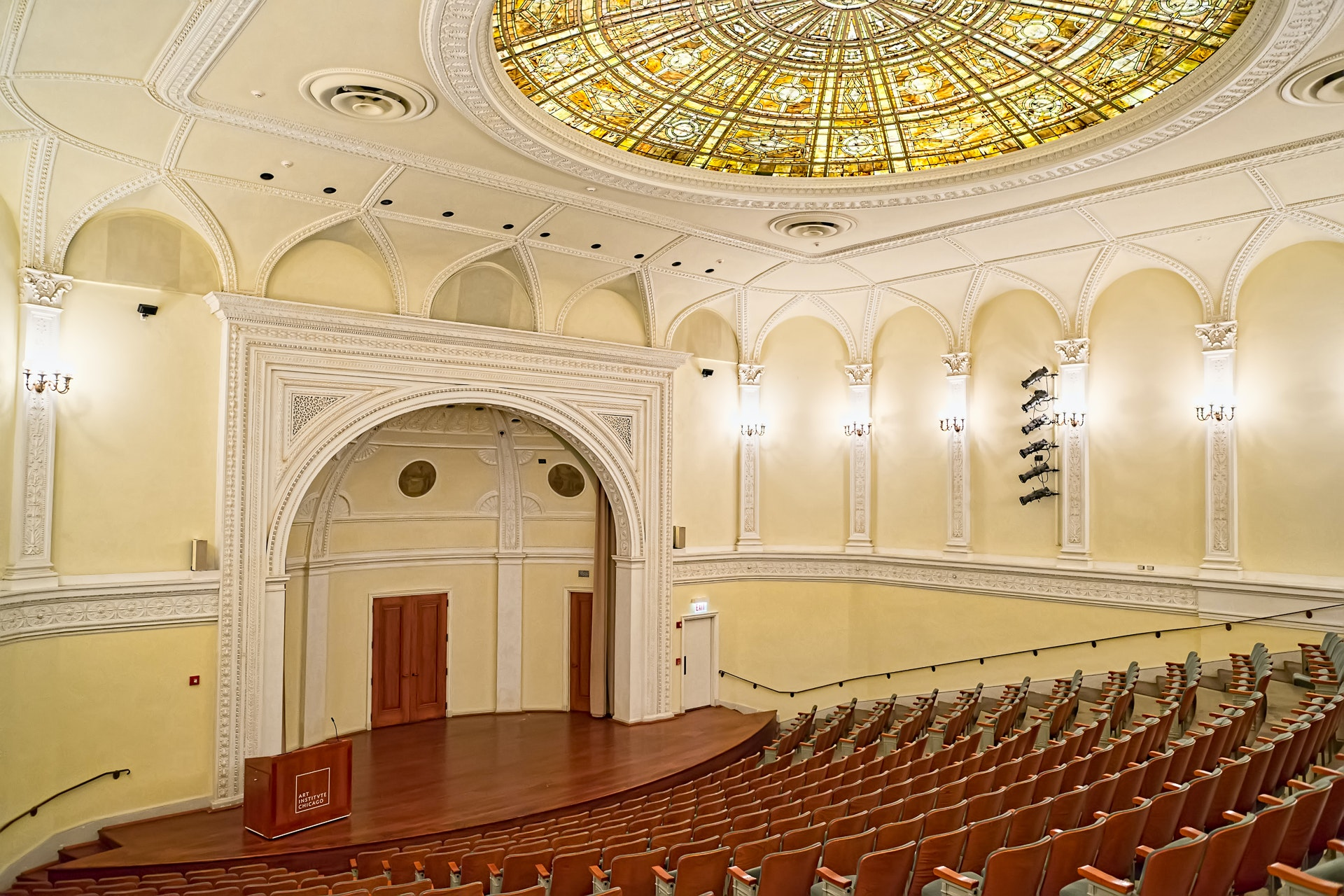 A large auditorium with a yellow glass dome ceiling