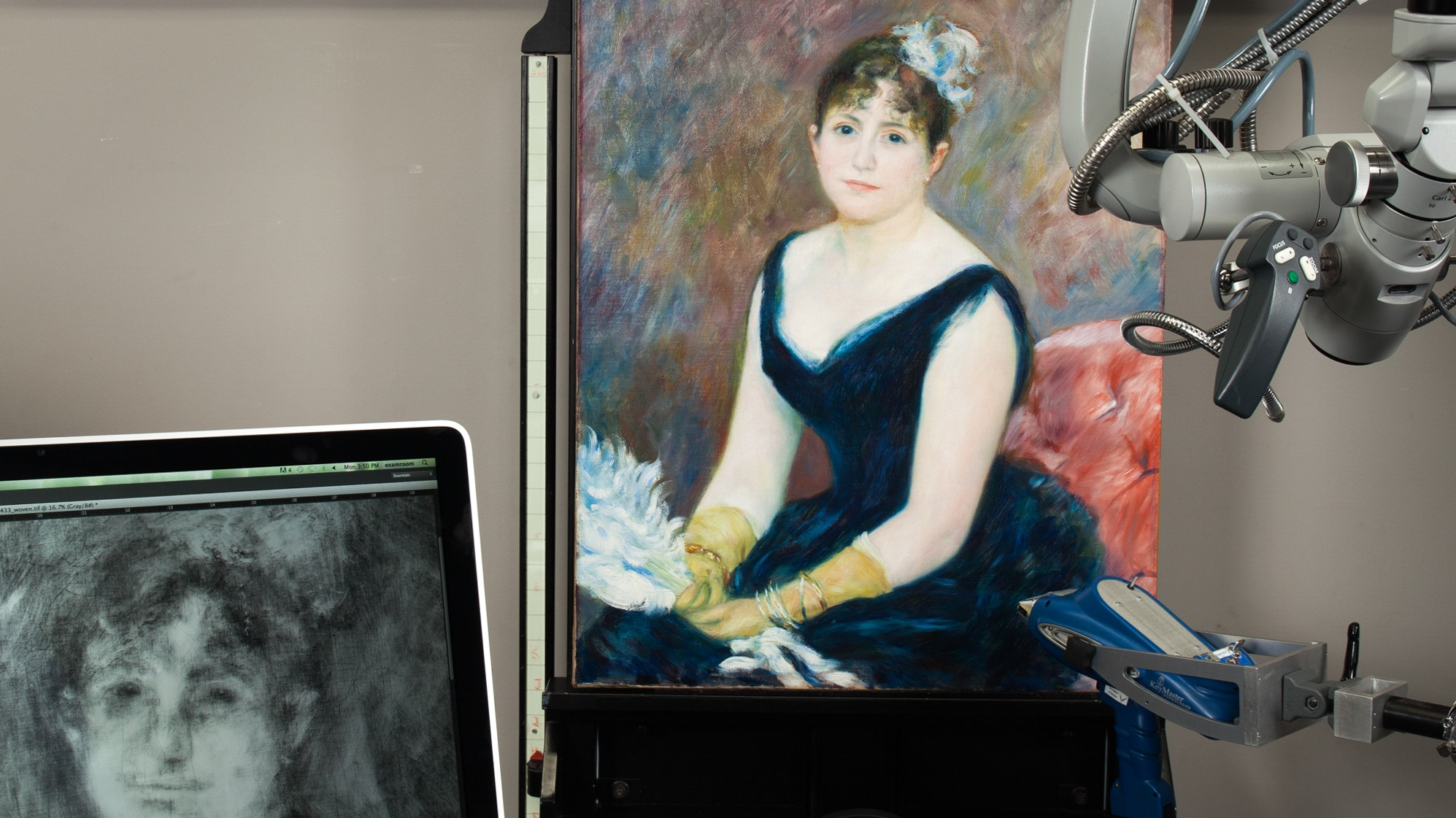 A painting is being scanned by a large machine. An alternate view of the painting is seen in an adjacent computer screen.