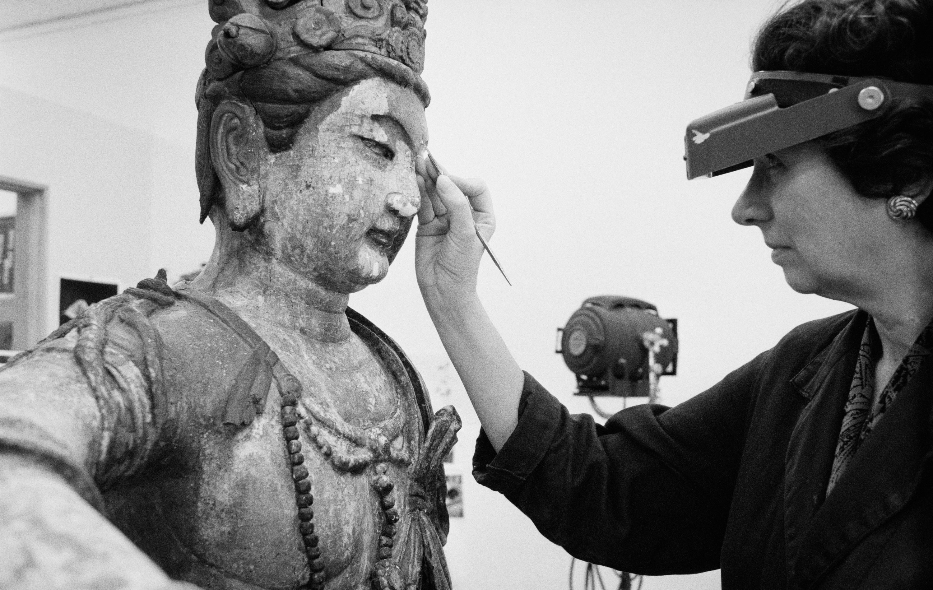 A conservator works on a Chinese sculpture using a hand tool.
