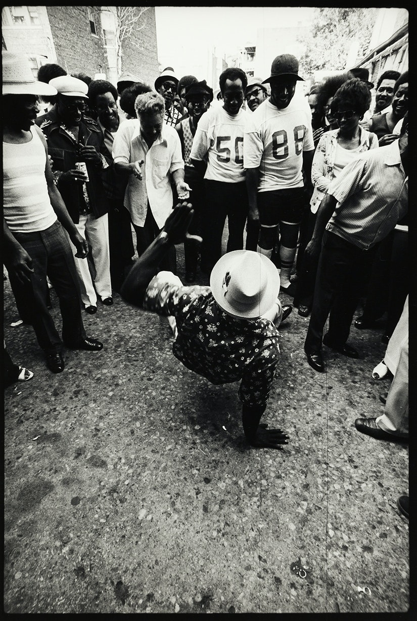 Man dancing in the center of a group of people