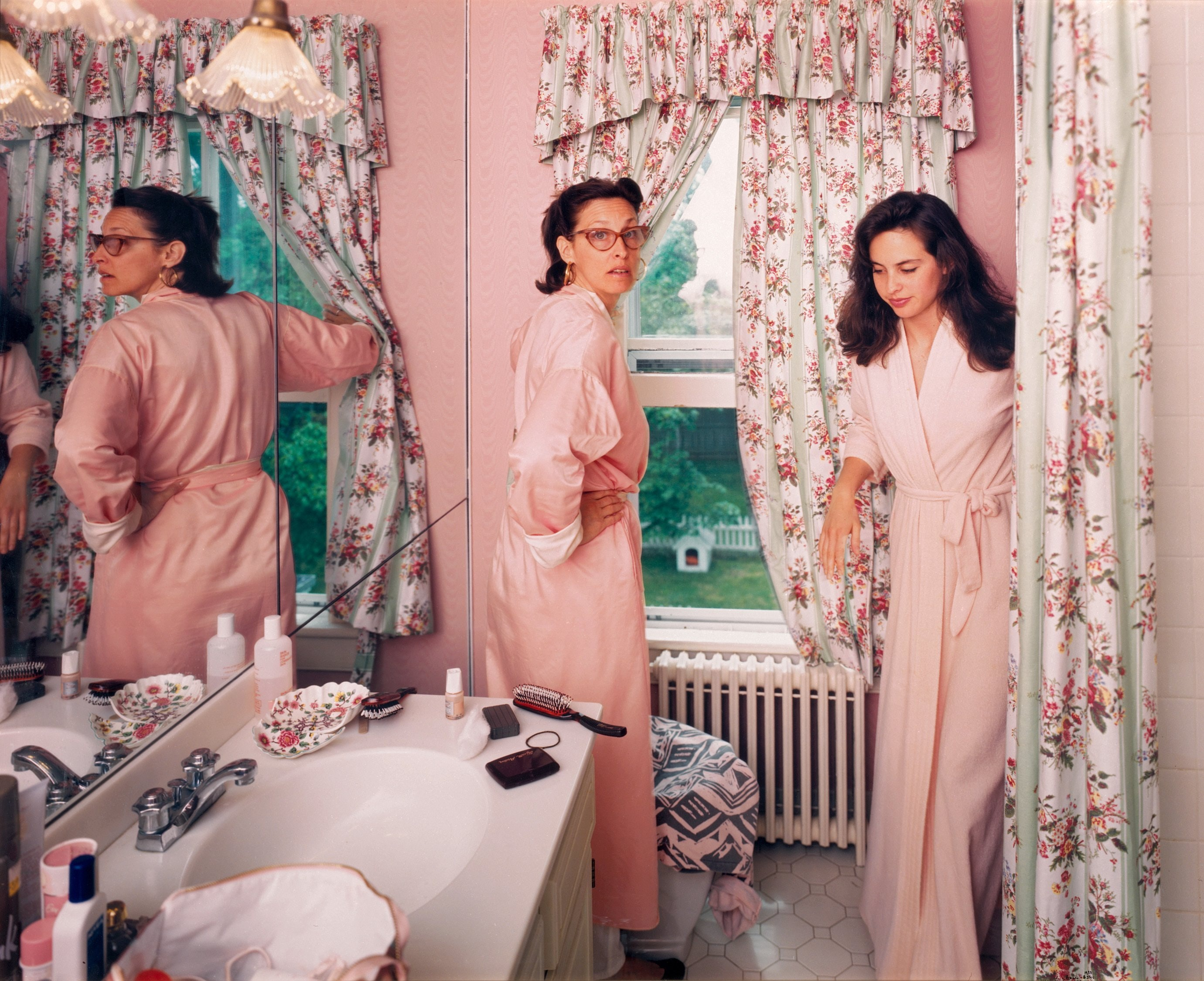 Two women in pink robes get ready in a pink bathroom.