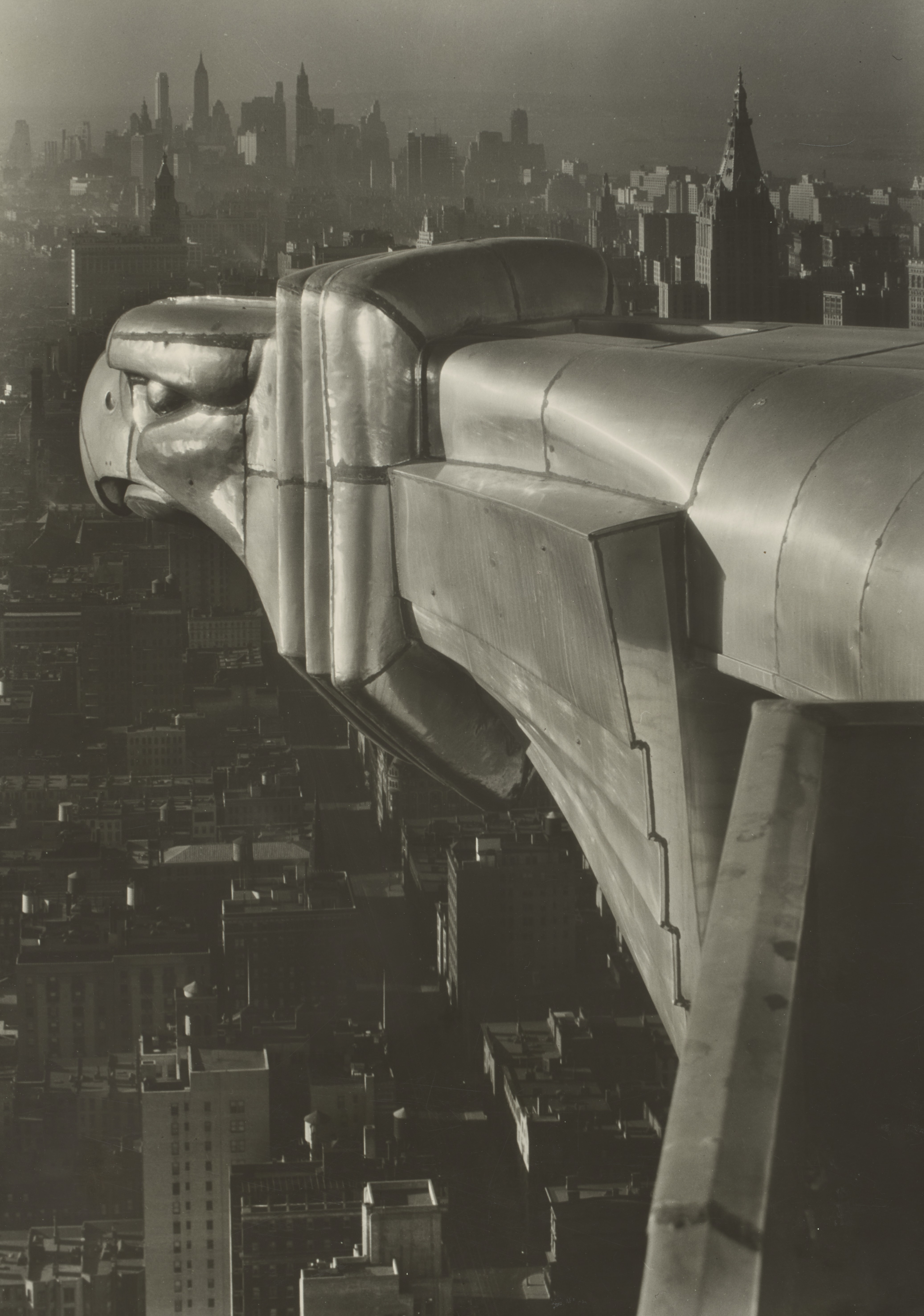 A black-and-white photograph shows one of the gargoyles of the Chrysler Building, other New York skyscrapers fading into the background.