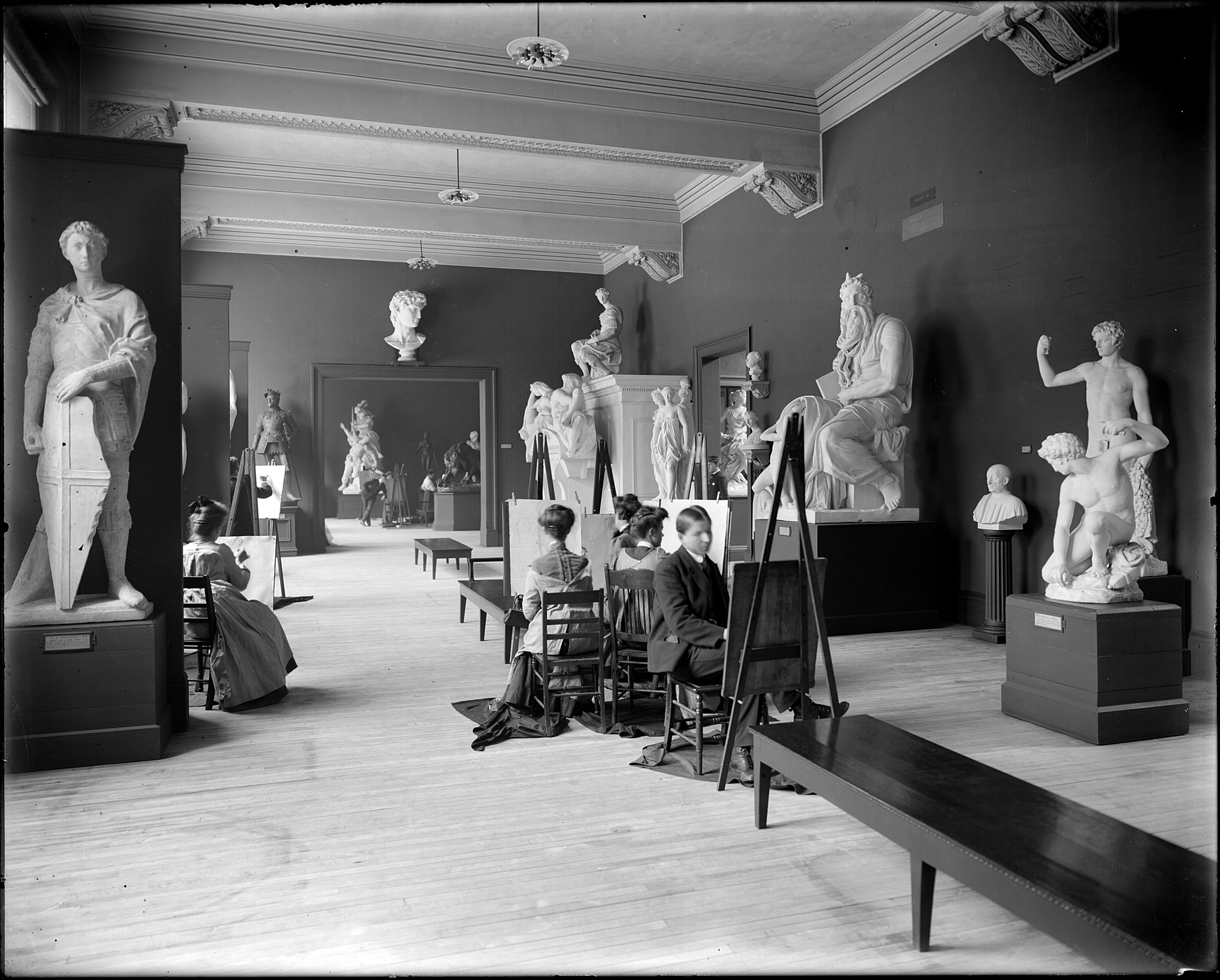 Early photograph of people painting in the galleries amidst plaster replicas of classical and Renaissance scuilptures