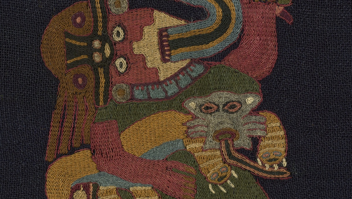 Embroidered on a black textile is a human figure holding a pampas cat has a snake-like creature coming from its mouth.